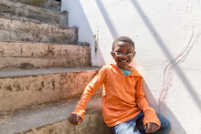 Smiling Boy On Concrete Steps