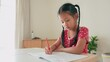Asian little girl sitting and studying writing at home with sunlight through the front door, self learning homeschooling