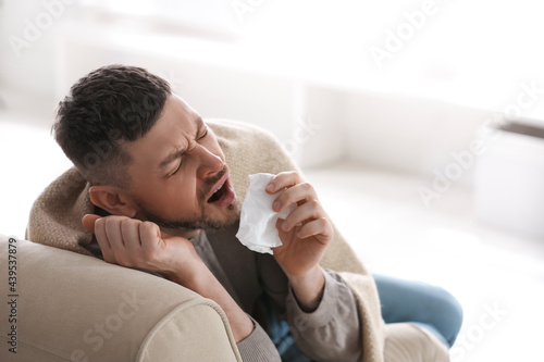 Fototapeta Man suffering from runny nose at home