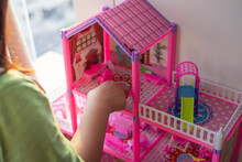Pink Doll House With A Child Playing With It.