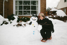 Boy Hugging Snowman In Front Of House