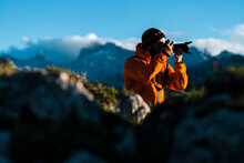 Adult Hiker Using Digital SLR Camera In Craggy Mountains