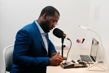 Young Entrepreneur Taking Notes While Making A Podcast