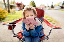 Boy In Camp Chair With Cards