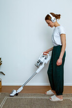 Young Woman In Headphones Using Modern Vacuum Cleaner At Home