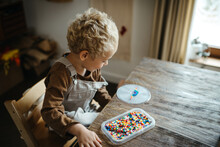 Blond Boy Playing With Iron Beads At A Rustic Wooden Table