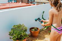 Crop Girl In Swimwear Watering Plants With Hosepipe