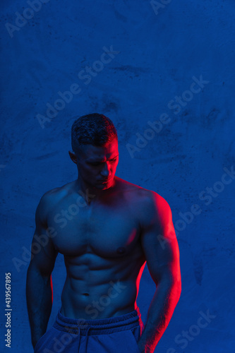 Fototapeta premium Bodybuilder is posing in the colorful neon light