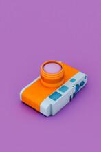 Orange And Blue Camera On Violet Background- Vertical Image