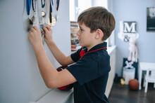 A Young Boy Examines His Medals.