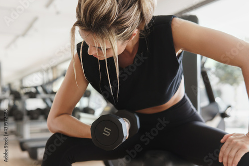 Fototapeta Athletic woman doing bicep curl exercise with a dumbbells in the gym