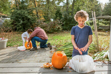 Boy Makes Disgusted Face At Slimy Pumpkin Seeds