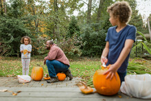Girl Holds Hands Full Of Pumpkin Seeds With Family