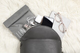 Stylish urban backpack with different items on white faux fur, flat lay