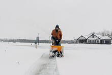 Clearing Snowy Driveway With A Snowblower.