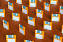 Pattern Of Blue And Orange Floppy Disks On Brown Background Arranged Differently