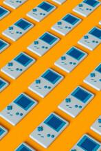 Pattern Of Blue 8-bit Handheld Game Console Layed On Orange Background