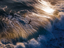 A Surfer Jumping Off A Wave