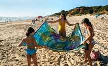 Kids Spreading Towel Out On The Beach