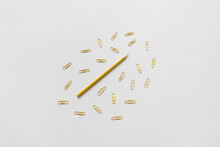 Yellow Pencil And Paper Clips On Gray Background