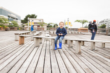 Boy Sits On Outdoor Wooden Bench
