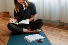 Woman In Background Journaling With Bible And Essential Oil In Foreground