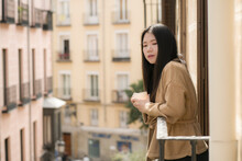 Young Contemplative And Beautiful Asian Woman At Home Or Hotel Balcony - Thoughtful Korean Girl Having Morning Coffee Enjoying Street View Thinking Relaxed