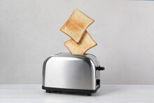 Bread Slices Popping Up From Modern Toaster On White Wooden Table