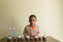 Black Boy Blows Out Candles On Birthday Cupcakes.