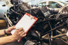 Man Writing On A Clipboard In A Garage. Professional Motorcycle Mechanic Working In Bike Repair Service