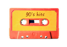 An Old Vintage Cassette Tape (obsolete Music Technology) With The Handwritten Text: 90's Hits. Light Red Plastic Body, Vivid Orange Label, Isolated On White.