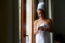 Smiling Woman In Towels Texting On Her Phone