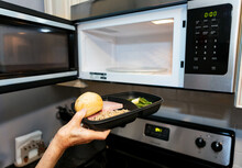 Meal: Woman Puts Delivered Meal Into Microwave To Warm