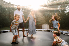 Family Jumping On Trampoline Together