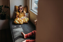 Young Girl Girl With Pink Heart Sunglasses And Princess Dress Sitting At Home.