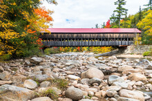 Old Wooden Covered Bridge With A Red Metal Roof Spanning A Mountain River On A Partly Cloudy Autumn Day. Beautiful Fall Foliage. White Mountain National Forest, NH, USA.