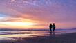 Zwei Frauen spazieren während des Sonnenuntergangs den Strand entlang