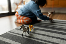 Little Girl Playing With Horses And Dinosaurs