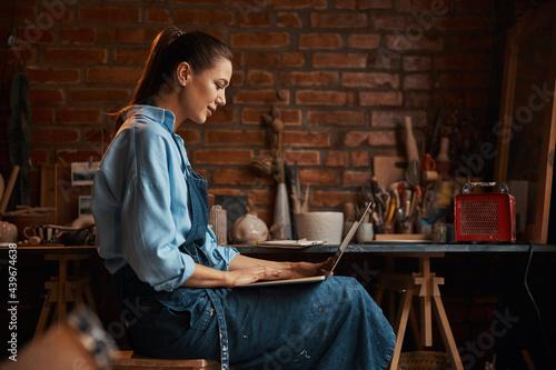 Fotografija Happy smiling elegant craft woman wearing uniform looking to the screen of noteb