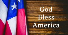 Composition Of Text God Bless America With American Flag On Wood Background