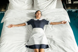 Happy young chambermaid in uniform lying on large double bed