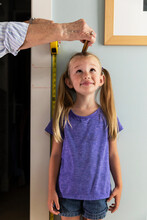 Young Girl Measuring Her Height With Tape Measure