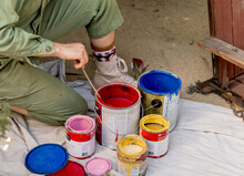 Woman Checks Red Paint Flow Before Working