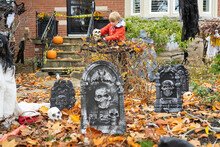 Boy Setting Up Grave Yard Scary Halloween Decorations In Front Yard