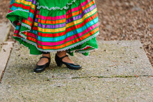 Cropped View Of A Girl With A  Traditional Mexican Dress Showing Her Dance Shoes