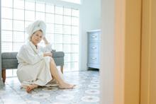 Woman In Bathrobe Sitting In A Bathroom