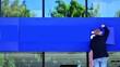 Leinwandbild Motiv Man standing on a ladder, putting a new, blue poster at sign board