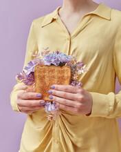 Woman Holding Sandwich With Purple Flowers