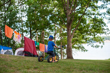 Boy On A Tricycle In Front Of Tents And Clothesline