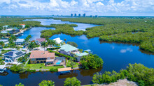 Aerial Bay View With Homes In Florida And High Rises In The Background Surrounded By Blue Water
